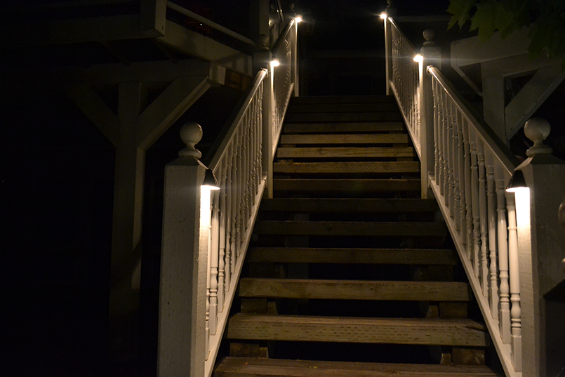 stairs with lights under railing
